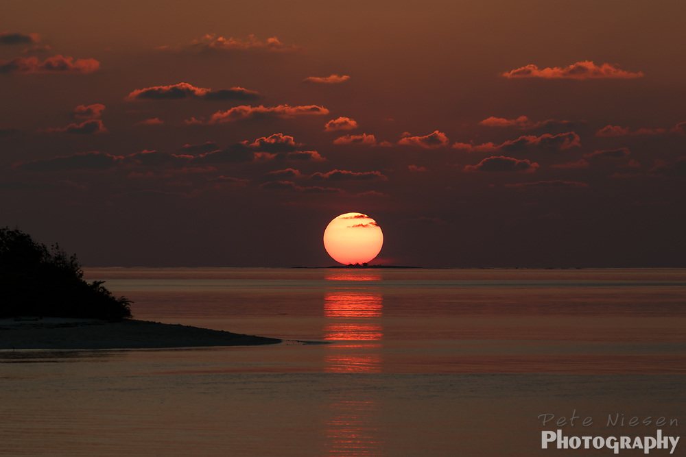 Big round red sun sinking into the ocean on the horizon at sunset