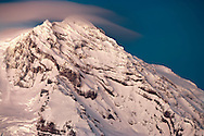 One of three summits of Mount Rainier in winter (Point Success) including the South Tahoma Glacier Headwall with a Cumulus Lenticularis cloud starting to form above the peak. Viewed from the SW. Mount Rainier National Park, WA, USA