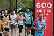Two male runners support a struggling female participant during the finale 600 metres of The Virgin London Marathon at Birdcage Walk on 28th April 2019 in London in the United Kingdom. Now in it's 39th year, the London Marathon is a large sporting event with over 40,000 runners expected to take part.