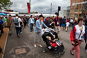 London 2012 Olympic Park in Stratford, East London. Crowds of fans, young and adult walking around the site.