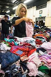 London, June 14th 2017. As fire rages through a residential tower block, Grenfell Tower, in Kensington, West London, local residents show their generosity as well-wishers pour into the Maxilla Social Club with clothing, food, water and blankets for the residents of the block who will have lost everything. PICTURED: Volunteers sort through the clothes brought in by wellwishers