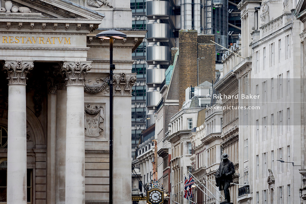 The statue of civil engineer James Henry Greathead (1844 – 1896), renowned for his work on the London Underground railway stands beneath the tall buildings at Cornhill in the City of London, the capital's financial district (aka The Square Mile), on 26th March, 2018, in London, England.