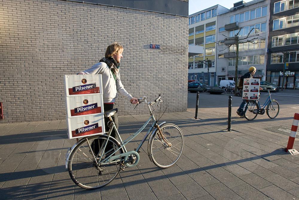 Nederland Rotterdam 21-03-2009 20090321Foto: David Rozing ..Rotterdam centrum, Jongens vervoeren lopend kratten bier die zij op het bagagerek geplaatst hebben. Guys trnasporting beers on bicycle for a party.Foto: David Rozing