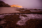 Lights illuminate the San Onofre Nuclear Generating Station in California, before dawn. Pacific Ocean waves wash seaweed and kelp up onto the beach in the foreground.