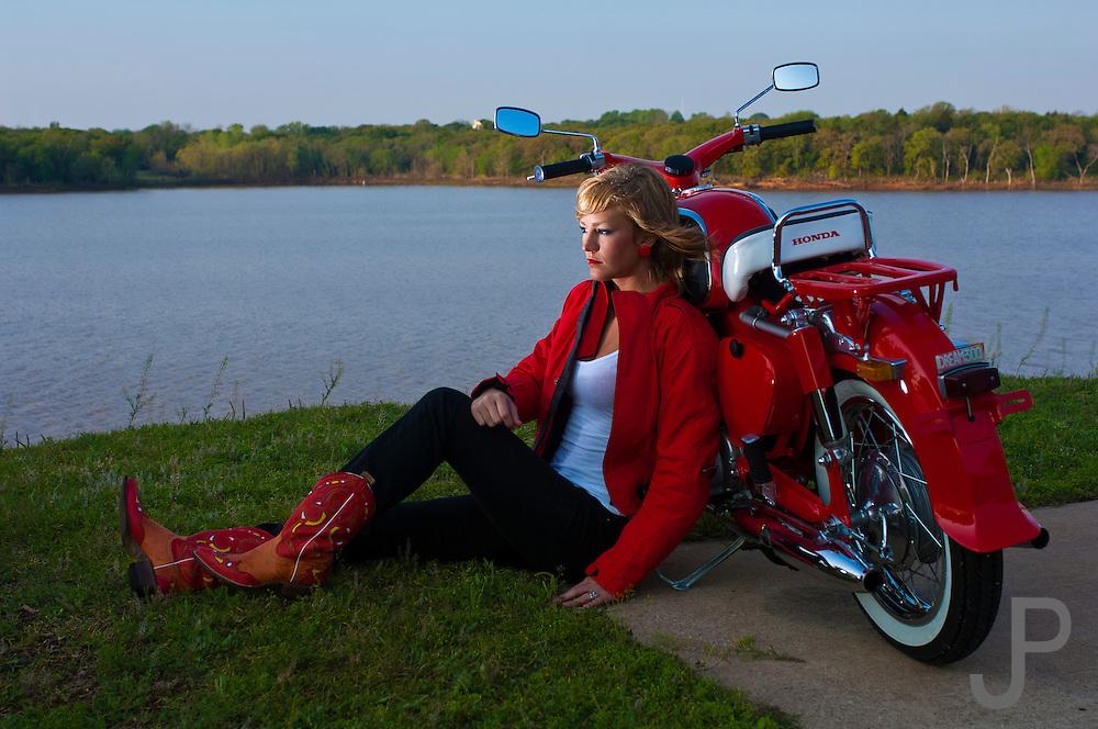 Model Mykie Oyler (model released) watching sunrise with her beautifully restored red 1960 Honda 305 Dream motorcycle (product released) at Arcadia Lake near Edmond, Oklahoma.