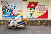 28 MARCH 2012 - HO CHI MINH CITY, VIETNAM:  People in front of billboards with revolutionary slogans and portraits of Ho Chi Minh, leader of Vietnam through its war for independence in Ho Chi Minh City, Vietnam. Ho Chi Minh City, which used to be known as Saigon, is the largest city in Vietnam and the commercial hub of southern Vietnam.    PHOTO BY JACK KURTZ