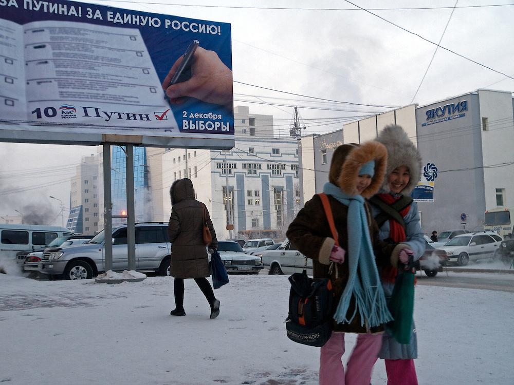Kinder vor einer Plakatwand zur Duma Wahl von V. Putins Partei Einheitliches Russland in Jakutsk. Jakutsk hat 236.000 Einwohner (2005) und ist Hauptstadt der Teilrepublik Sacha (auch Jakutien genannt) im Foederationskreis Russisch-Fernost und liegt am Fluss Lena. Jakutsk ist im Winter eine der kaeltesten Grossstaedte weltweit mit bis zu durchschnittlichen Wintertemperaturen von -40.9 Grad Celsius.<br /> <br /> Children in front of a billboard of Vladimir Putins United Russia party for the Duma elections. Yakutsk is a city in the Russian Far East, located about 4 degrees (450 km) below the Arctic Circle. It is the capital of the Sakha (Yakutia) Republic (formerly the Yakut Autonomous Soviet Socialist Republic), Russia and a major port on the Lena River. Yakutsk is one of the coldest cities on earth, with winter temperatures averaging -40.9 degrees Celsius.