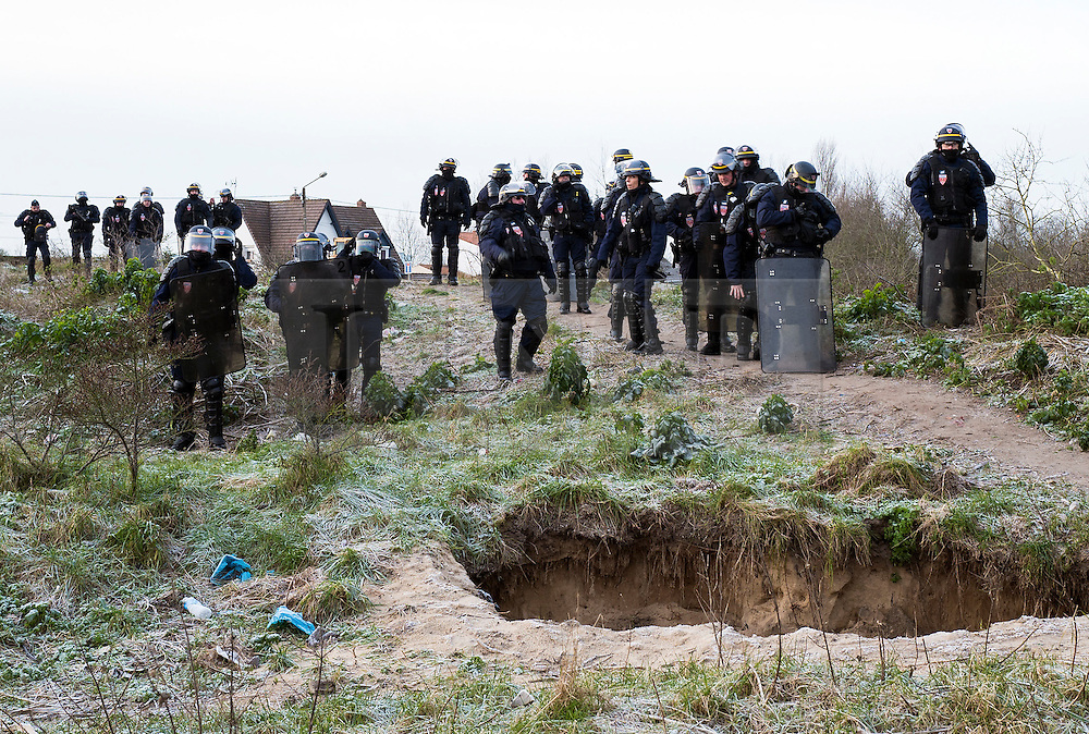 © London News Pictures. 18/01/16. Calais, France.  Riot police prepare to enter the Calais 'Jungle' to evict up to one thirdof the camp. French authorities are to bulldoze a 100-metre 'buffer zone' between the camp and the adjacent motorway, which leads to the ferry port. Photo credit: Rob Pinney/LNP