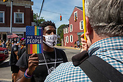A demonstrator holds an ACLU in front of a counter-protester during the Mifflinburg Pride Event.