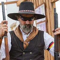 Participant carries his weapons for inspection after his competition during the Cowboy Action Shooting European Championship in Dabas, Hungary on August 11, 2012. ATTILA VOLGYI