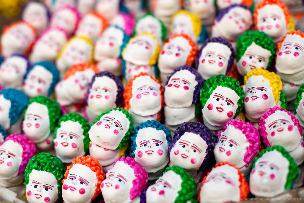 A strange amalgamation of finger like puppets with white painted faces, and colorful hair and cheeks.