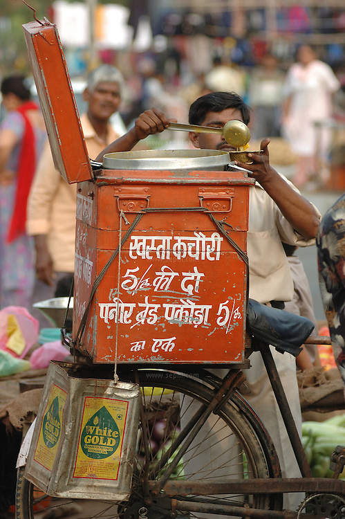 A vendor selling hot kachori and vegetable curry at the RK Puram market in south Delhi. The metal box on the back of his bicycle has a portable stove to keep the food hot.
