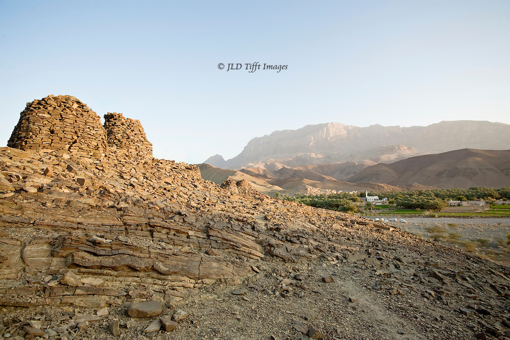 View of Wadi el Ayn ( Ain ), Oman, showing hill topped by Iron Age beehive tombs; in the distance, a village, and beyond a mountain, under a clear pale blue sky.
