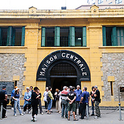 Tourists standing on the sidewalk in front of the main entrance to Hoa Lo Prison museum. Hoa Lo Prison, also known sarcastically as the Hanoi Hilton during the Vietnam War, was originally a French colonial prison for political prisoners and then a North Vietnamese prison for prisoners of war. It is especially famous for being the jail used for American pilots shot down during the Vietnam War.