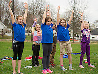 Elm Street School students do stretching exercises following the Tiger Trek at Leavitt Park on Friday morning.  (Karen Bobotas/for the Laconia Daily Sun)