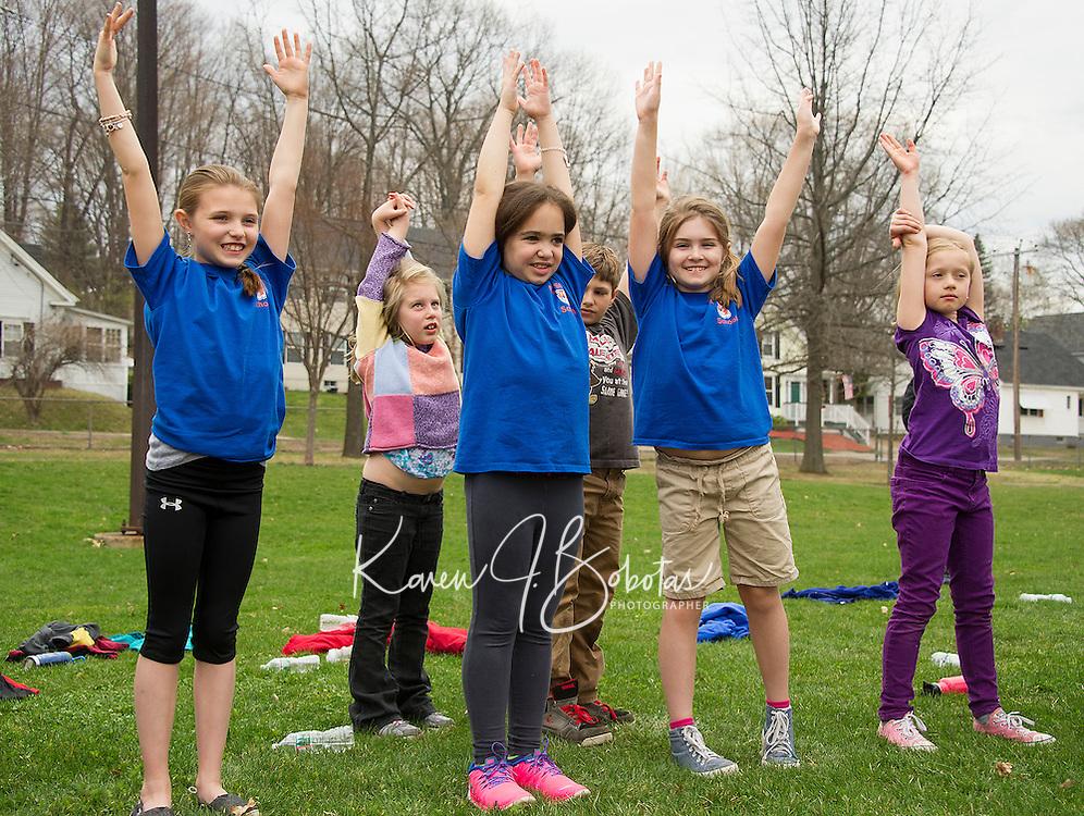 Elm Street School students do stretching exercises following the Tiger Trek at Leavitt Park on Friday morning.  (Karen Bobotas/for the Laconia Daily Sun)