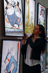 """© Licensed to London News Pictures. 31/03/2017. London, UK. A staff member inspects """"For He's a Jolly Good Fellow"""" by Gerald Scarfe, (Est. GBP 3-5k), depicting George Osborne.  Press preview of """"Made in Britain"""" at Sotheby's in New Bond Street.  The auction on 5 April celebrates innovative British art in the twentieth century as well as artwork by political cartoonist Gerald Scarfe. Photo credit : Stephen Chung/LNP"""