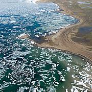 Ice hangs on around the edge of an inland lake near Cambridge Bay, Nunavut, Canada