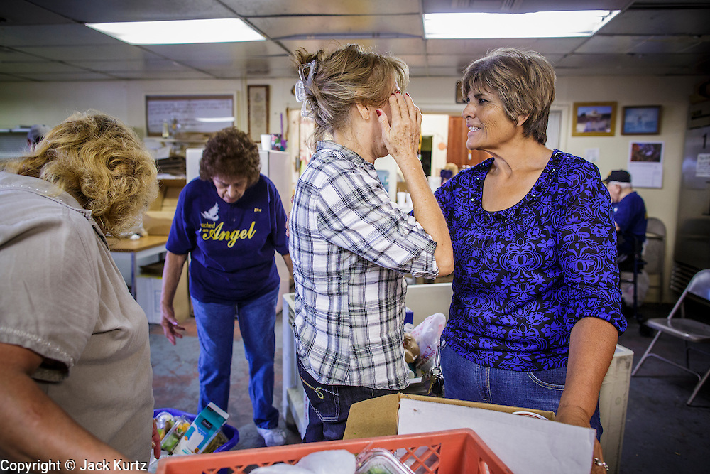 07 AUGUST 2012 - TOLLESON, AZ: BLANCA COREA (right) the Assistant Director at the food bank in Tolleson, AZ, comforts a client Tuesday. The Tolleson food bank has been operating for more than 20 years. It used to serve mostly the families of migrant farm workers that worked the fields around Tolleson but in the early 2000's many of the farms were sold to real estate developers. Now the food bank serves both farm worker families and people who lost their homes in the real estate crash, that his Phoenix suburbs especially hard. More than 150 families a day are helped by the Tolleson food bank, an increase of more than 50% in the last five years.   PHOTO BY JACK KURTZ