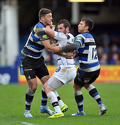 Anderson Neisen (Brive) is double-tackled by Matt Banahan and Gavin Henson (Bath) - Photo mandatory by-line: Patrick Khachfe/JMP - Tel: Mobile: 07966 386802 06/04/2014 - SPORT - RUGBY UNION - The Recreation Ground, Bath - Bath Rugby v Brive - Amlin Challenge Cup.