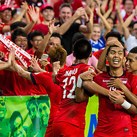 Khairul Amri (#19) of Singapore is embraced by his teammates after scoring a goal against Malaysia during the group stage match of the AFF Suzuki Cup at the National Stadium at the Singapore Sports Hub on November 29, 2014, in Singapore.