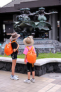 Sisters (11 years old, 8 years old) with hula dancer sculptures at Kona International Airport. Big Island, Hawaii