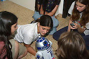 Children aged 13 playing with a robot in the shape of R2D2 from star wars