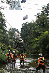 Denham, UK. 24 July, 2020. Swan, an environmental activist from HS2 Rebellion, and her possessions fall suddenly as her safety line above the shallow river Colne is released by a police officer from an ancient alder tree to which she had been attached for almost fourteen hours in an attempt to protect it from destruction during works for the HS2 high-speed rail link. Officers from Hampshire Police Marine Support Unit look on. An activist had been hospitalised when a safety line had been released in this way the previous day.