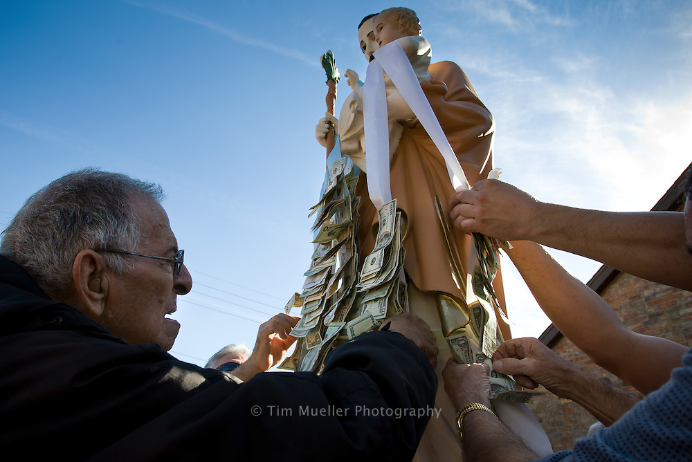 St. Joseph Society members pin money to the statue of St. Joseph before processing through the town of Independence, La. Aside from family gatherings, Mater Dolorosa Catholic Church is the primary place where Italian families gather in Independence.