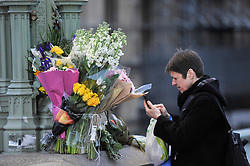 © Licensed to London News Pictures. 22/03/2018. LONDON, UK.  A woman looks at floral tributes on Westminster Bridge. A projection at dusk of the words #LondonUNITED will be seen on the Houses of Parliament on the first anniversary of the Westminster terror attack.  The projection is part of the #LondonUNITED tribute initiative by the Mayor of London to the victims in the terror attacks in the capital in 2017.  Similar projections will take place on the first anniversary of the terror attacks which took place at London Bridge, Finsbury Mosque and Parsons Green.  Photo credit: Stephen Chung/LNP