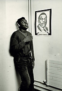Youth listening to Walkman, standing in front of Marcus Garvey poster. Photo by Richard Saunders 1983