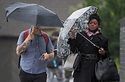 © Licensed to London News Pictures. 13/06/2021. London, UK. Member son the public brave the wet conditions at Queens Park in north west London at rush hour, on another grey and damp summer's day. Photo credit: Ben Cawthra/LNP