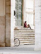 Woman on phone sat outside Santa Maria del Popolo, Rome, Italy
