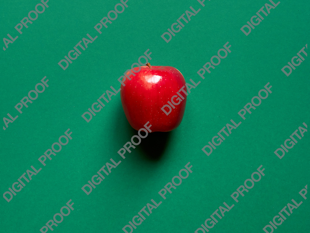 Red apple viewed from above over a green background isolated in studio