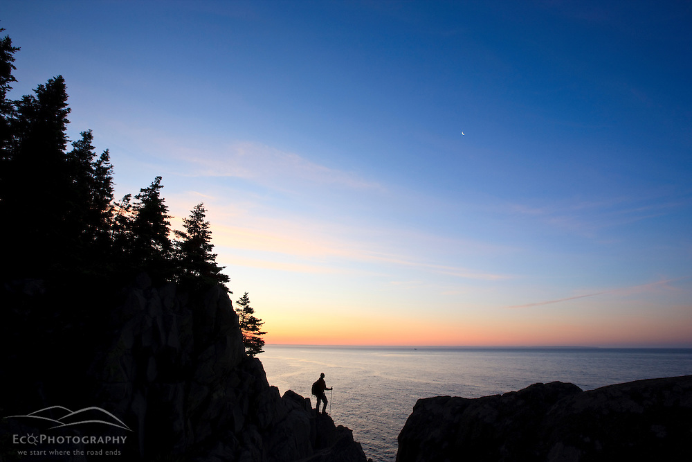A lone hiker at sunrise on the Bold Coast trail in Cutler, Maine.