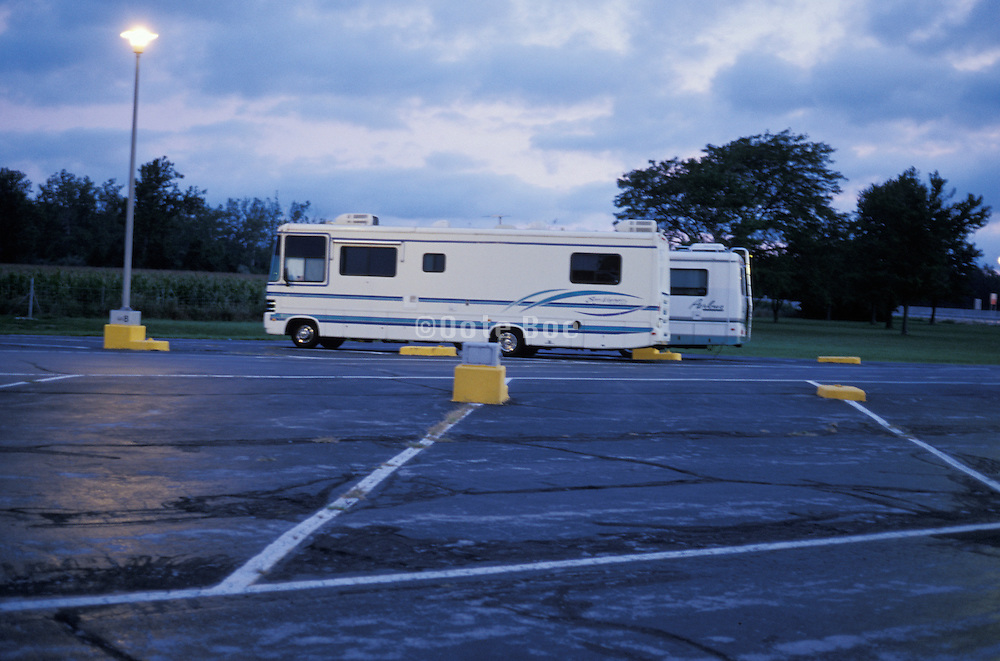 2 motor homes parked in a lot