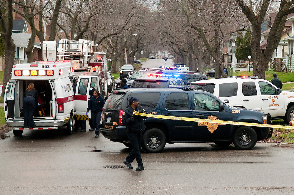 Matt Dixon | The Flint Journal..Police tape off the scene of a shooting at Mason and W. Paterson Streets in Flint while a male in his early 20s is treated inside an ambulance before being taken to Hurley Medical Center, Friday evening. The victim was listed in serious condition.