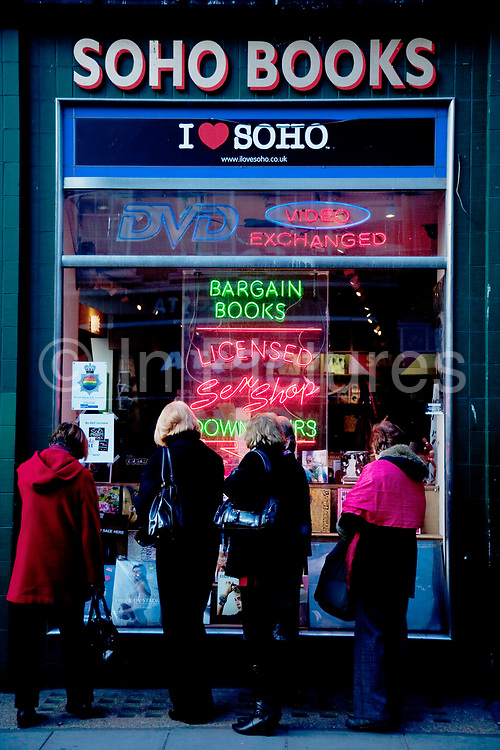 Ladies look into the window of the Soho Books sex shop on Old Compton Street. London. This shop sells art and photography books as well as having a licensed sex shop downstairs as the neon sign suggests.