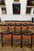 rows of chairs placed in front of a wall with classic portrait paintings