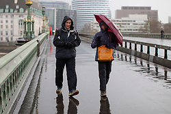 © Licensed to London News Pictures. 04/04/2019. London, UK. A couple walk across Westminster Bridge as heavy rain falls in Westminster. Photo credit : Tom Nicholson/LNP