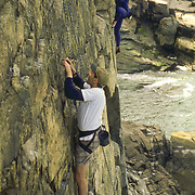 Rock climbers at the popular Otter Cliffs location in Acadia National Park, Maine