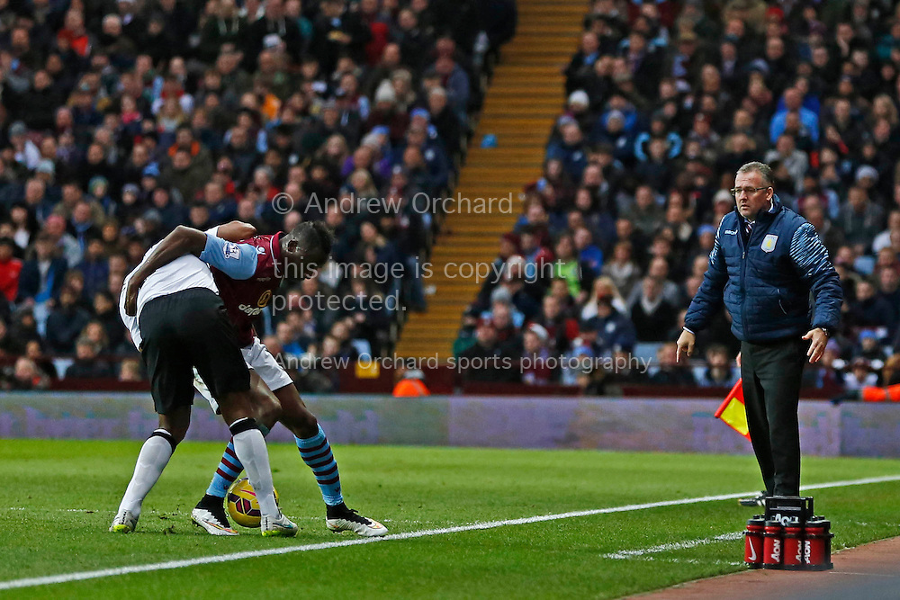 Aston Villa manager Paul Lambert watches on as his player Aly Cissokho (right) wrestles with Antonio Valencia of Manchester United.  Barclays Premier league match, Aston Villa v Manchester Utd at Villa Park in Birmingham on Saturday 20th December 2014<br /> pic by Mark Hawkins, Andrew Orchard sports photography.