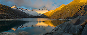 In golden light of sunset, Nevado Santa Cruz Norte (5829 m or 19,120 ft) reflects in Lake Cullicocha (4628 m or 15,174 ft). This was day 8 and camp 8 of 10 days trekking around Alpamayo in Huascaran National Park (UNESCO World Heritage Site), Cordillera Blanca, Andes Mountains, Peru, South America. This panorama was stitched from 3 overlapping photos.