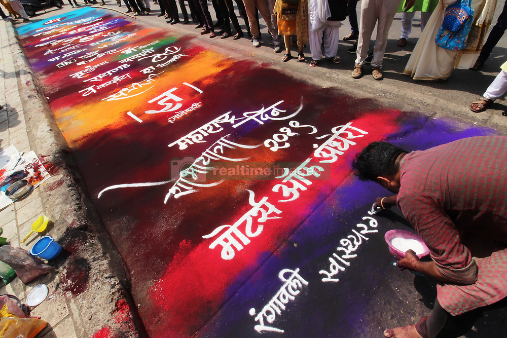 """May 1, 2019 - Mumbai, India - Artist Dr. Tejas Lokhande gives a final touch to a 'Rangoli' or a mural made from coloured powders outside a railway station on the occasion of """"Maharashtra Day"""" in Mumbai, India on 01 May 2019. """"Maharashtra Day"""" is a state holiday in the Indian state of Maharashtra, commemorating the formation of the state of Maharashtra from the division of the Bombay State on 1 May 1960. (Credit Image: © Himanshu Bhatt/NurPhoto via ZUMA Press)"""