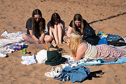 Portobello, Scotland, UK. 3 April 2021. Easter weekend crowds descend on Portobello beach and promenade to make the most of newly relaxed  Covid-19 lockdown travel restrictions and warm sunshine with uninterrupted blue skies. Pic;  Four young women relaxing around a wood fire.  Iain Masterton/Alamy Live News