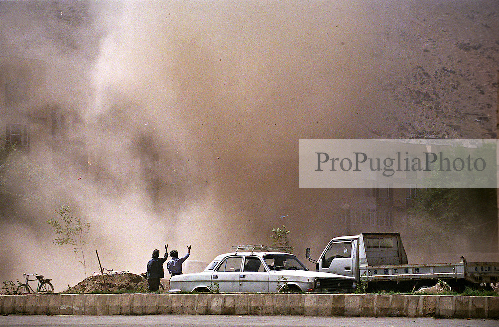 Two Afghan raise their hands towards the sandstorm