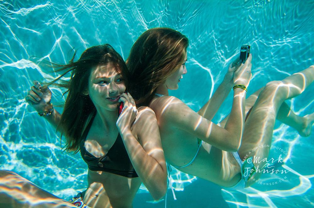 2 Teenage girls using mobile phones underwater in swimming pool people ****Model Release available