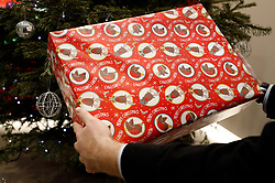 Embargoed to 0001 Friday December 26<br /> PICTURE POSED BY MODEL. A man about to open a Christmas present. Almost two out of three people receive a Christmas gift they do not like, but many are too polite to ask for it to be exchanged for something else, a new study has found.
