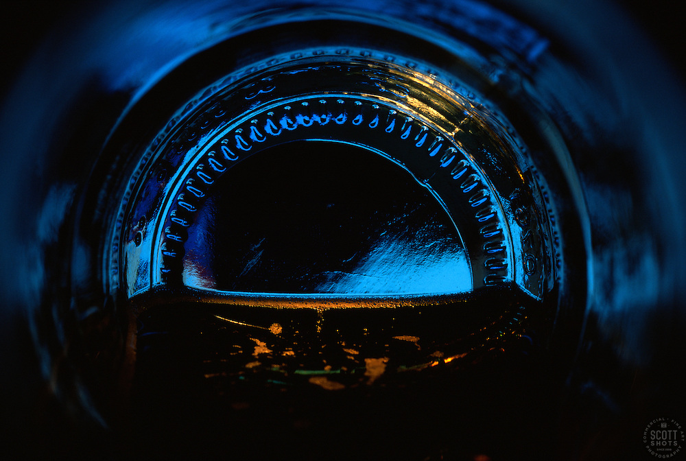 """""""Beauty at the Bottom: Moonlight""""- This image is a photograph of a beer bottle shot right down the mouth of the bottle. A television provides the main light source."""