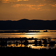 A golden sunset over the Ayeyarwaddy River, as seen from the top of Mandalay Hill, Mandalay, Myanmar.